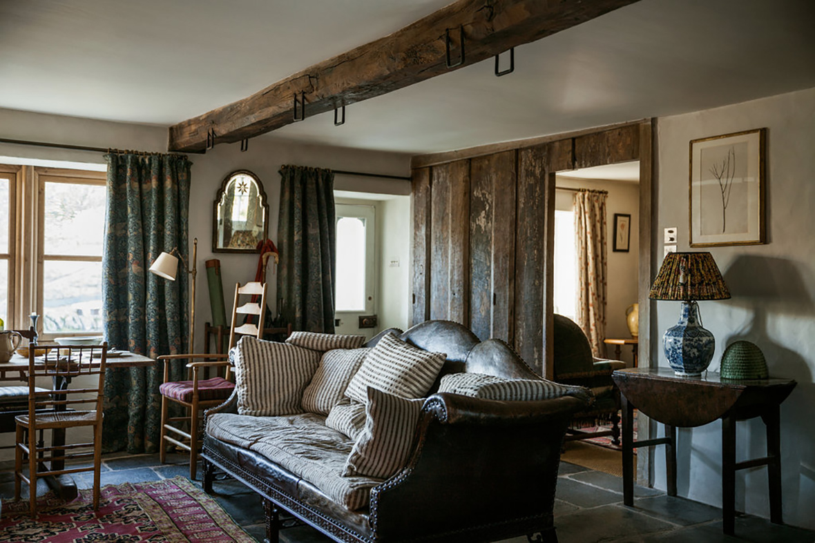 In The Living Room Of Docker Nook An Antique Camelback Leather Sofa Piled With Understuffed Down Cushions Late 19th Century William Morris Weave Curtains
